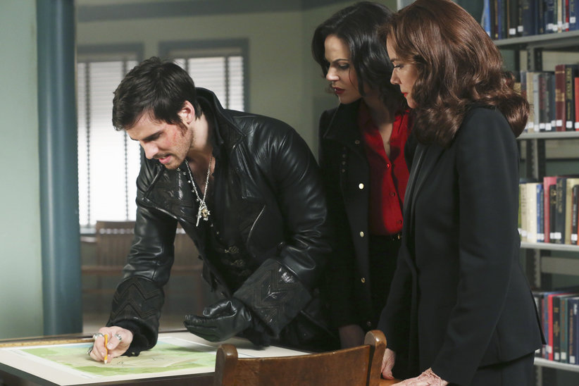 Captain Hook, Regina (The Evil Queen) and Cora study a map in the Storybrooke library.
